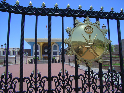 Hinter dem vergitterten Eingangstor mit dem vergoldeten Wappen des Sultanats Oman liegt der Königspalast