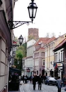 Die Burgstraße, in der sich Geschäfte und Restaurants aneinander reihen, ist die Flaniermeile von Vilnius. Im Hintergrund ist der rote Gediminas-Turm, das Wahrzeichen der Metropole, zu sehen.